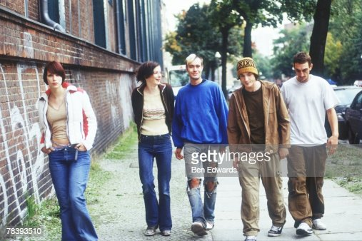 Friends walking down sidewalk : Stock Photo