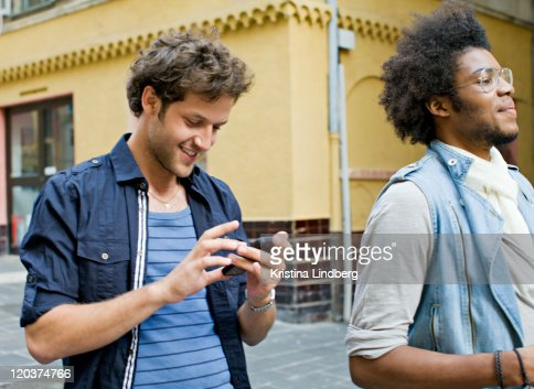 Friends walking down street, one checking phone. : Stock Photo