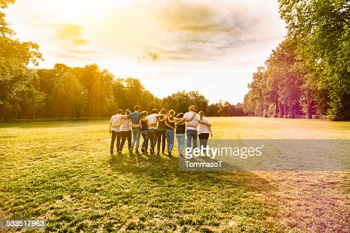 Friends walking in a park at sunset arm in arm