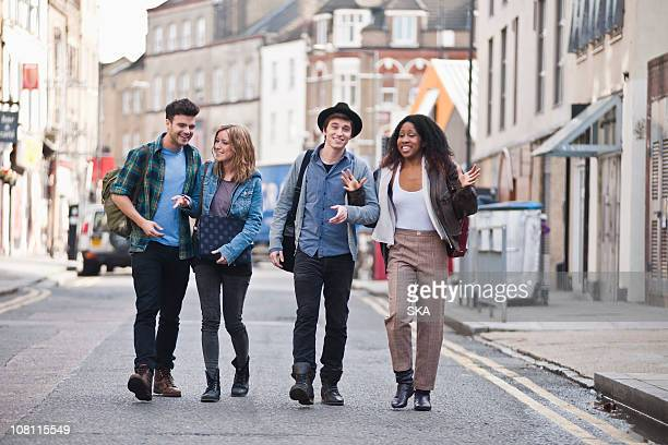 4 friends walking in street laughing