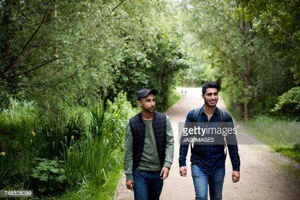 Friends walking on pathway in park