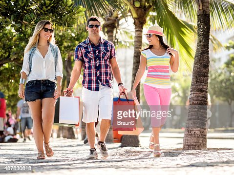 Friends walking on the street while coming back from shopping.