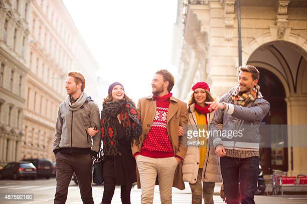 Friends walking outdoors in winter city.