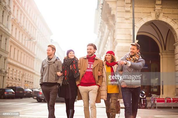 Friends walking outdoors in winter city.