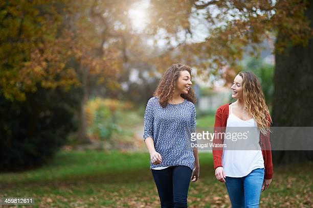 Friends walking through city park.