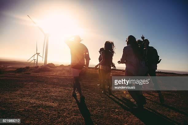 Amigos caminando hacia Vintage coche al anochecer en energía eólica