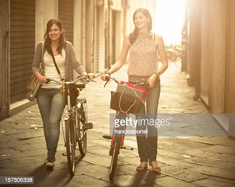 Friends walking with bicycle on narrow street - urban scene : Stock Photo