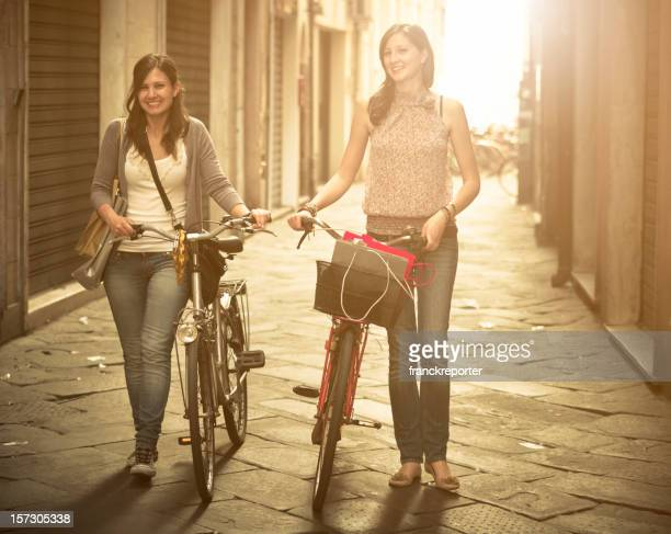 Friends walking with bicycle on narrow street - urban scene