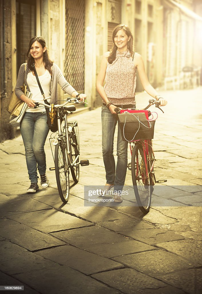 Friends walking with bicycle on narrow street - urban scene : Stock Photo