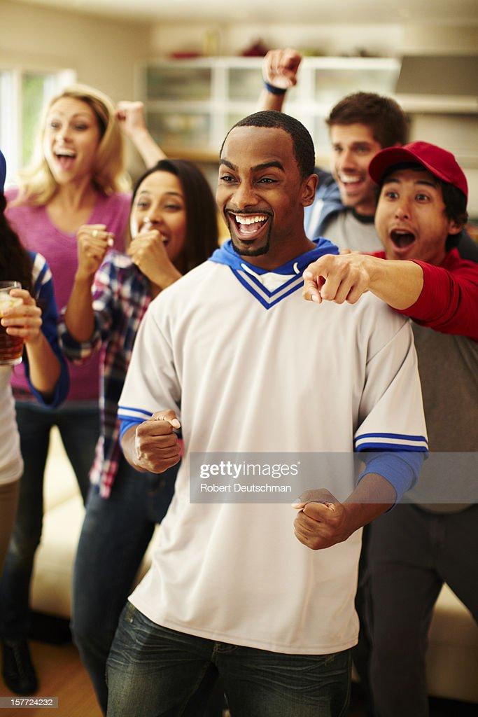 Friends watching baseball and cheering. : Stock Photo