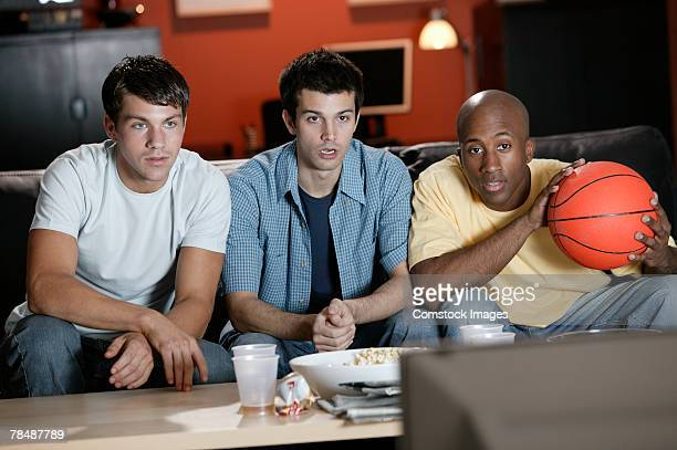 Friends watching basketball game in living room