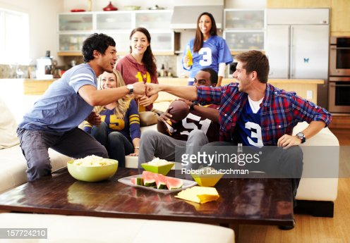 Friends watching football in living room.