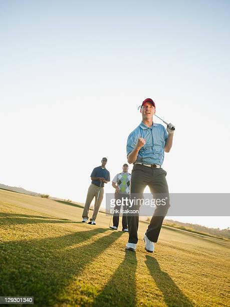 Friends watching golfer cheering