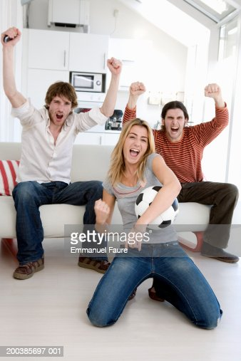 Friends watching soccer match on television, cheering at goal, : Stock Photo
