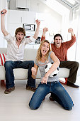 Friends watching soccer match on television, cheering at goal,