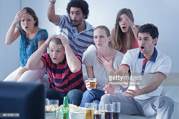 Friends watching sports match on television together express disappointment at team's performance