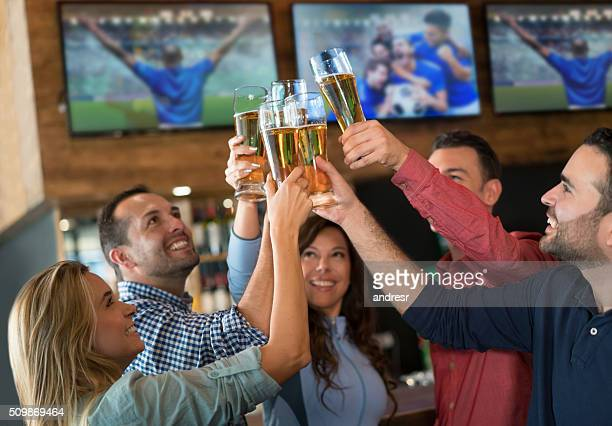 Friends watching the game and making a toast
