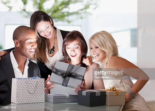 Amis en regardant une femme ouverte cadeau