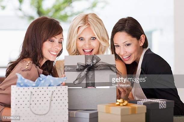 Amici guardando donna aprire regalo