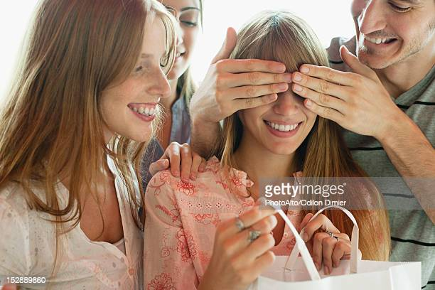 Friends watching young woman opening gift