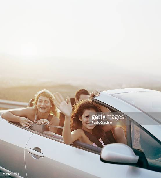 Friends Waving from Convertible