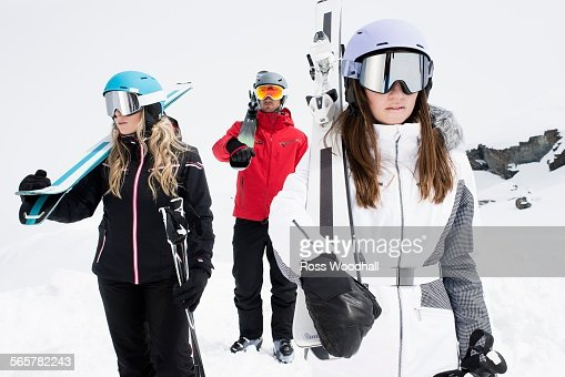 Friends wearing helmets and ski goggles holding skis, portrait