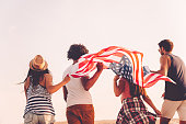 Rear view of four young people carrying american flag while running outdoors