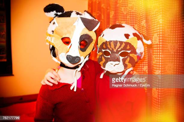 Friends With Arms Around Wearing Mask At Home
