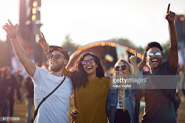 Friends with arms in the air at festival concert