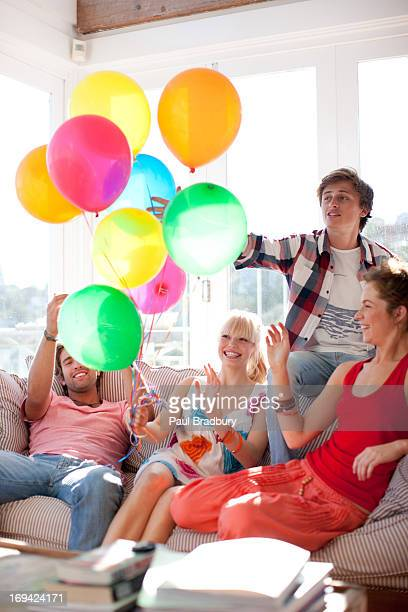 Friends with balloons sitting on sofa in living room