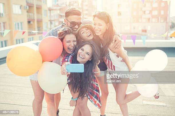 Friends with balloons taking selfie on the rooftop