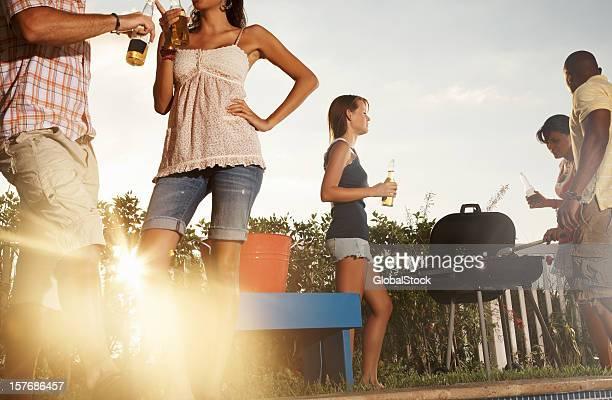 Amis avec barbecue et bouteilles de bière de profiter de leurs vacances