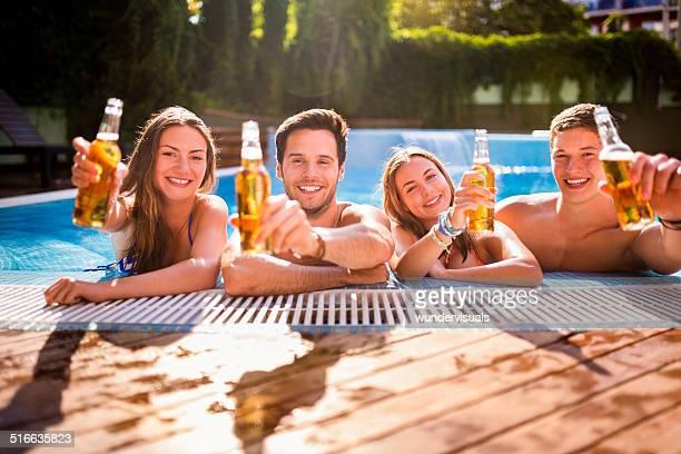 Freunde mit Bier am Pool