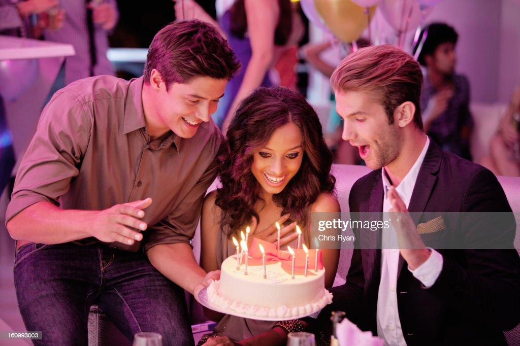 Friends with birthday cake in nightclub : Stock Photo