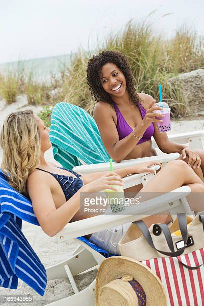 Friends With Bubble Teas Relaxing On Beach Chair
