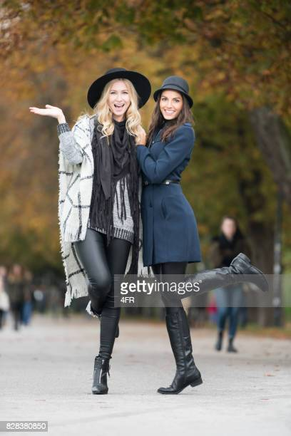Friends with candid smiles in a playful interactive pose, Outdoor Autumn Fashion