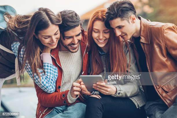 Friends with digital tablet sitting outdoors