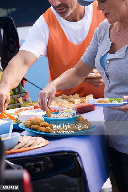 Friends with finger food at tailgate party