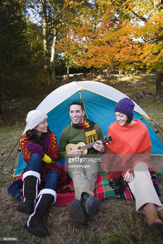 Friends with guitar by tent : Stock Photo