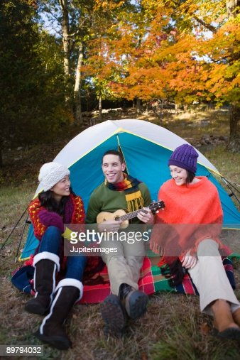 Friends with guitar by tent : Stockfoto