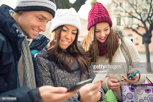 Friends With Shopping Bags Using Smart Phone On Street