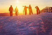 Group of friends with ski and snowboards walking against sunset