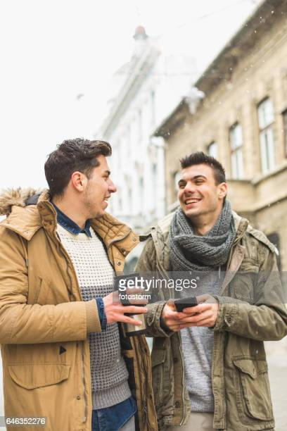 Friends with smart phone and travel mug