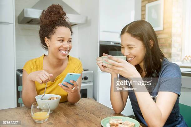 Friends with smartphone at breakfast