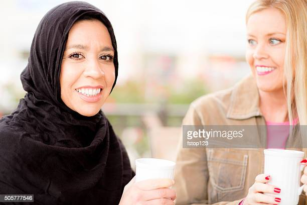 Friendship.  Muslim woman and her friend enjoy coffee together.