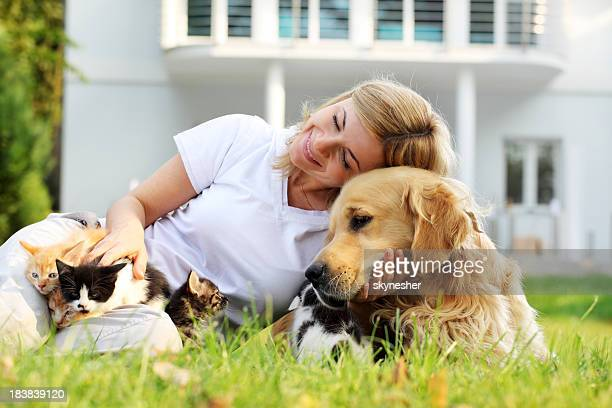 Friendship of cheerful woman with pets, dog and kittens.