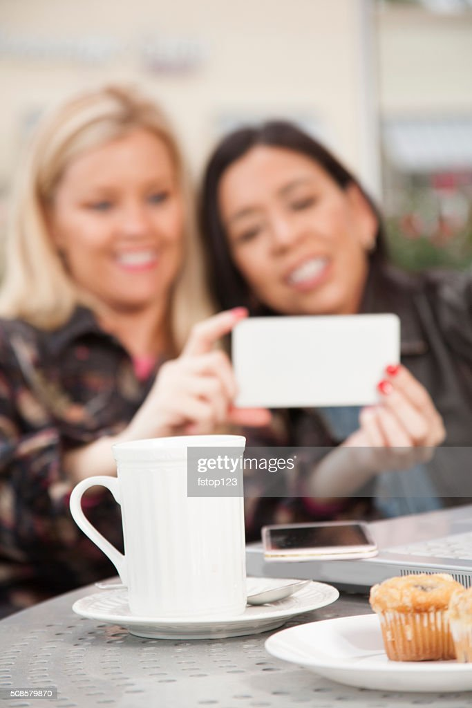 Friendship.  Women take selfies or view videos on cell phone. : Stock Photo
