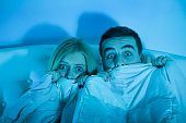 frightened couple watching a horror movie
