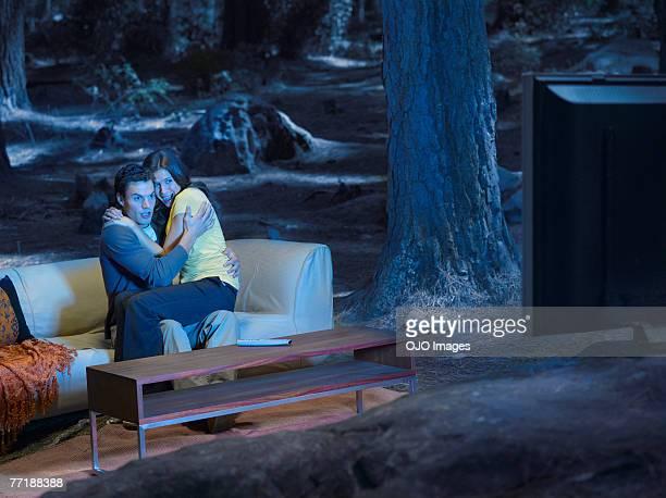 Ein ängstliches Paar vor dem Fernseher im Freien im Wald