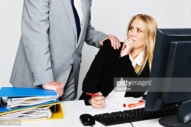 Frightened embarrassed young businesswoman is harassed by senior executive